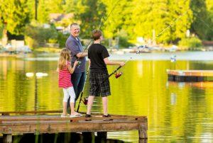 Onnellinen isä kalassa lastensa kanssa