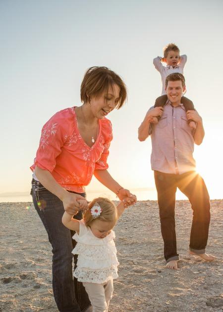 Aviopari lapsineen aurinkoisella hiekkarannalla