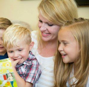Mormoniäiti perheineen lukemassa kirkon lastenlehteä