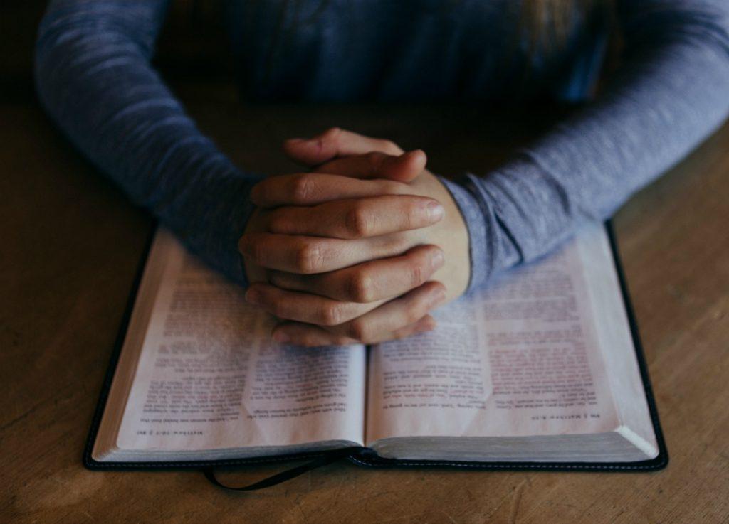 Henkilö rukoilemassa ja tutkimassa pyhiä kirjoituksia