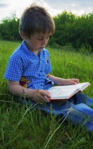 Lapsi lukee kirjaa nurmikolla