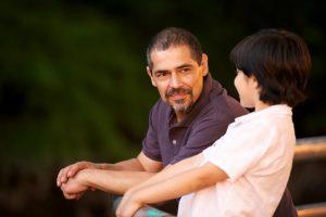 Isä ja poika keskustelevat ulkona