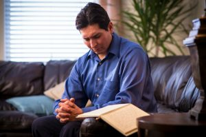Mies kirjoittaa päiväkirjaa ja rukoilee