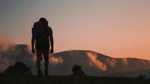 Mies patikoimassa vuorelle auringonlaskussa