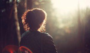 Nainen katsoo kohti auringonlaskua ulkona