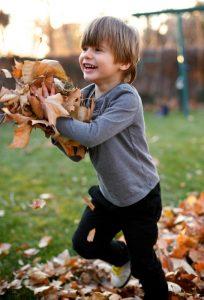 Iloinen lapsi leikki lehdillä ulkona