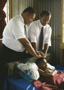 Kaksi afrikkalaista miestä antavat sairaalle siunauksen