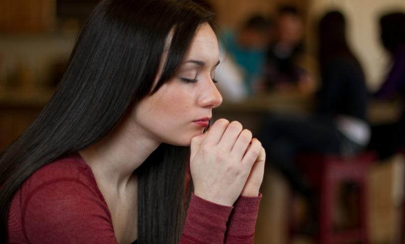 Nuori nainen polvillaan rukoilemassa
